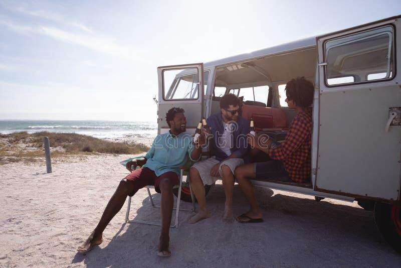 享用在露营者货车的海滩的小组朋友 免版税库存照片