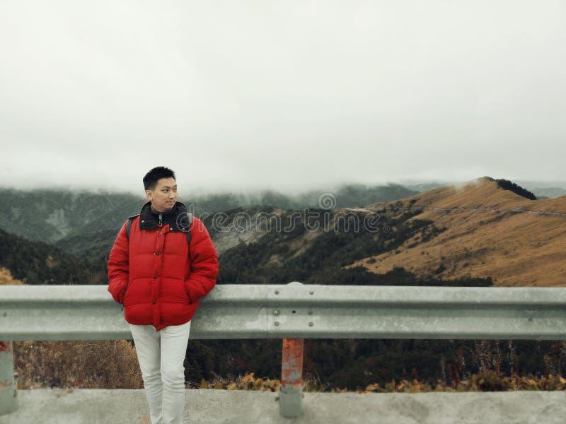 享用在风和薄雾的年轻亚裔人在山上面与美好的风景在背景中 免版税库存图片