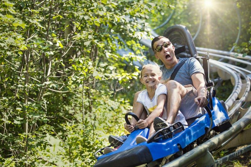享用夏天乐趣过山车的人和女孩乘坐 免版税库存图片