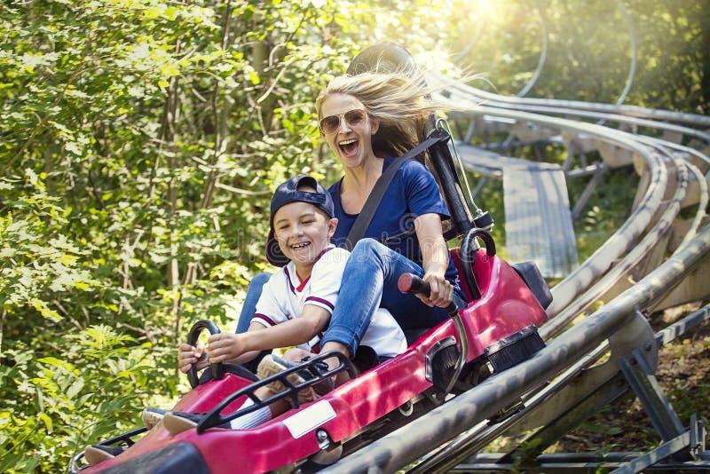 享用夏天乐趣过山车的妇女和男孩乘坐 免版税图库摄影