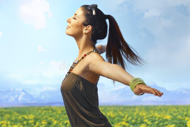享用夏天太阳的可爱的妇女户外 免版税库存图片