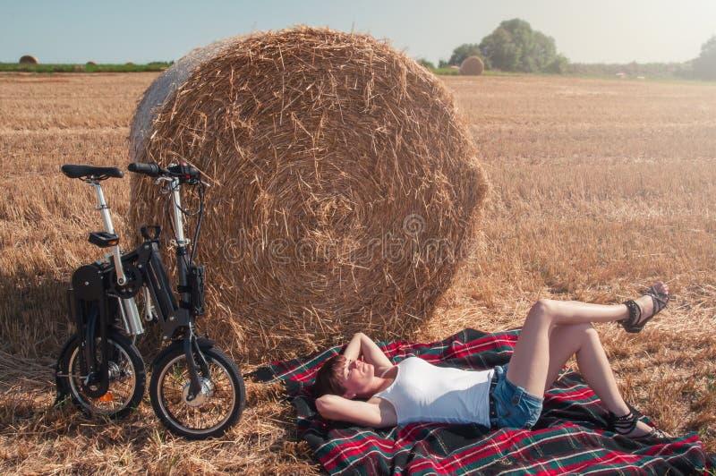 享用夏天太阳的年轻女人在国家 免版税库存图片