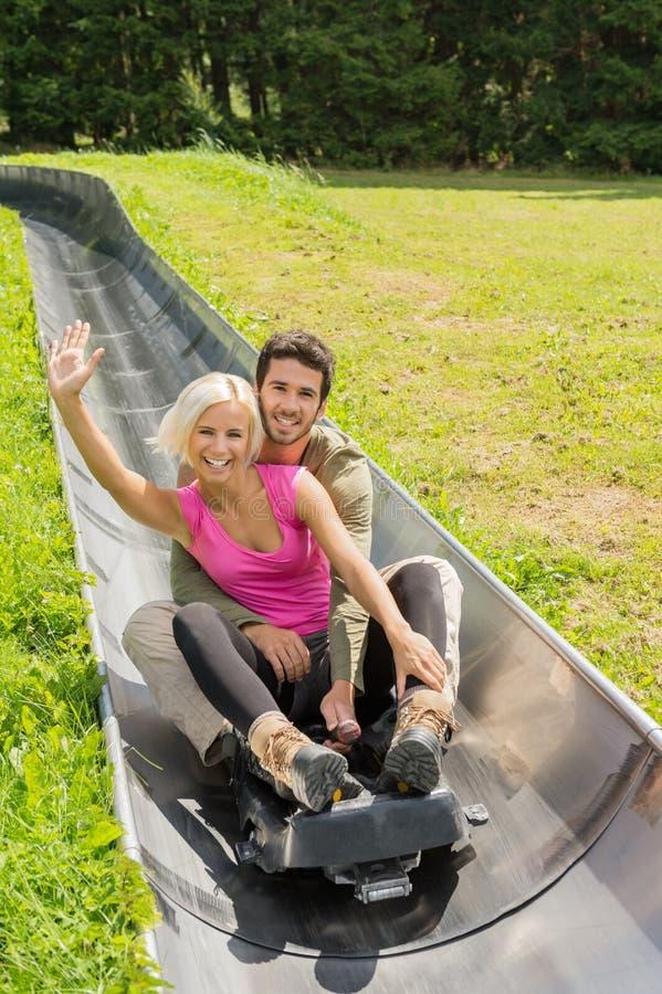 享用夏天爬犁的愉快的夫妇 免版税库存图片