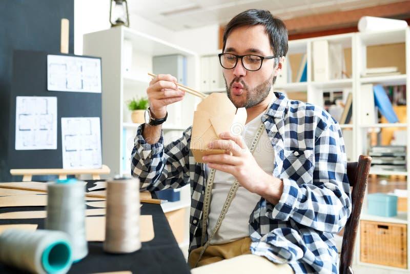 享用外卖食品的使变冷的设计师 免版税图库摄影