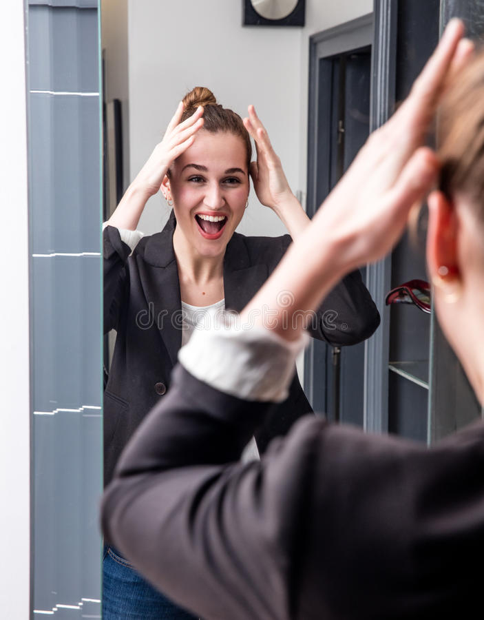 享用外向性年轻美丽的女商人在家看镜子 图库摄影