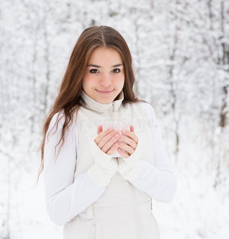 享用大杯子热的饮料的青少年的女孩在冷的天期间 库存照片