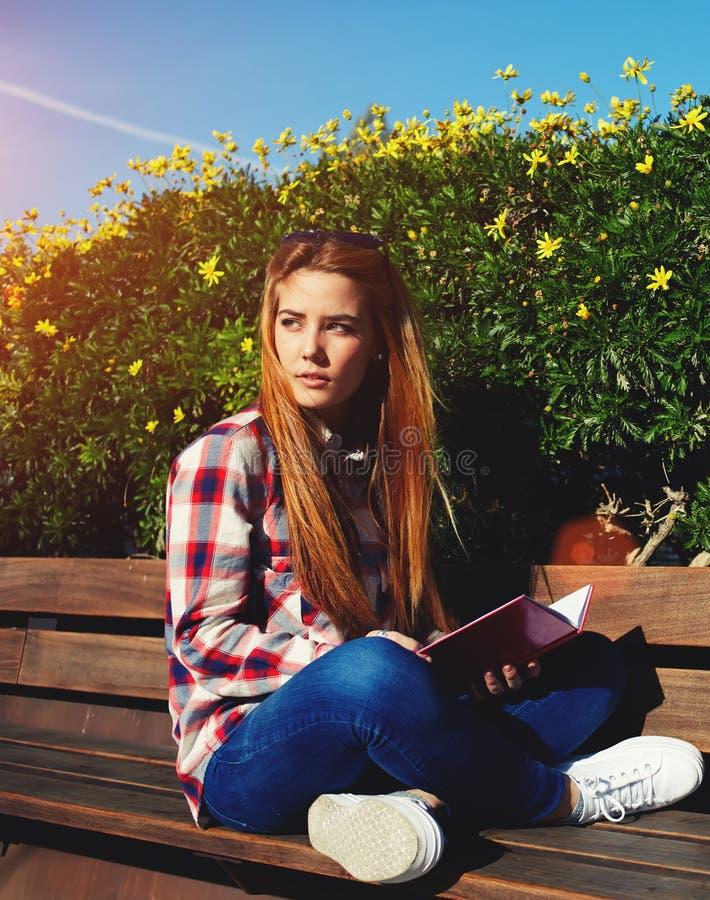 享用太阳的可爱的金发少妇美好的天户外 库存照片