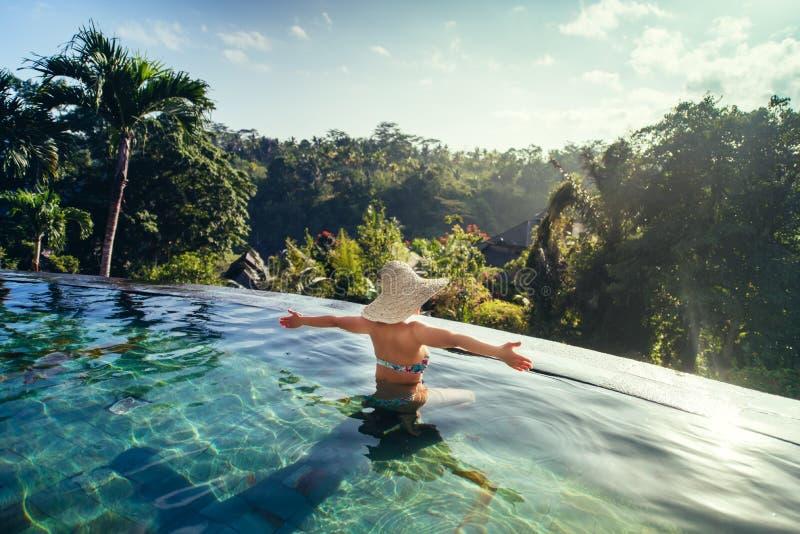 享用太阳的妇女在无限夏天游泳池在豪华手段 免版税库存图片