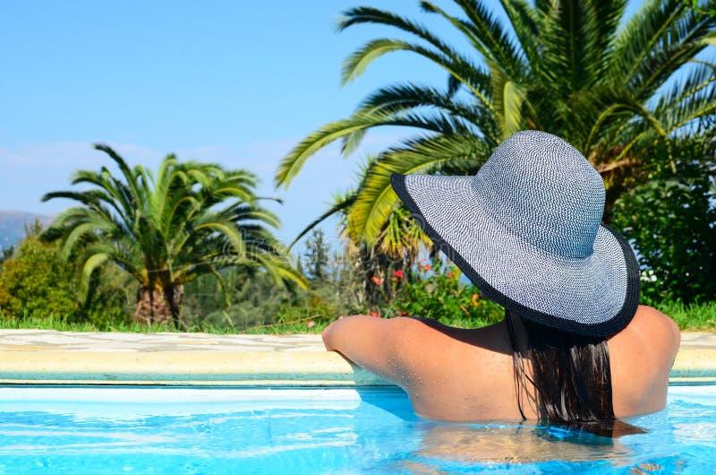 享用太阳的美女在游泳场 库存图片