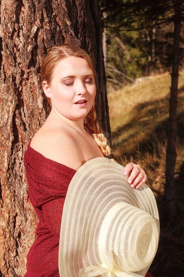 享用太阳的肥头大耳的年轻白肤金发的妇女 库存图片