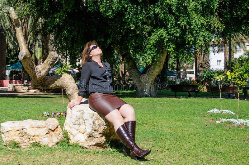 享用太阳的年轻端庄的妇女在公园 库存照片