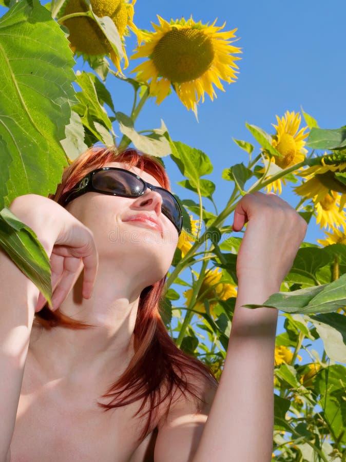 享用女孩头发红色坐的星期日向日葵下 库存图片