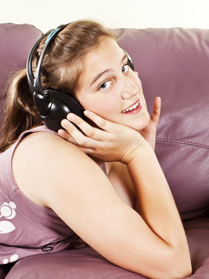 享用女孩耳机听的音乐年轻人 库存图片