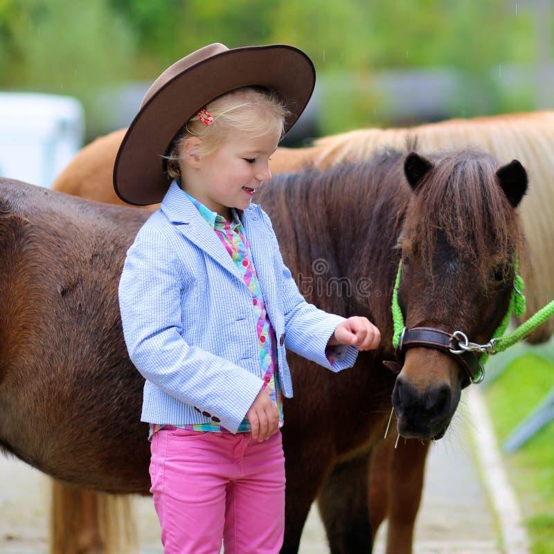 享用她的小马的小女孩 免版税库存图片