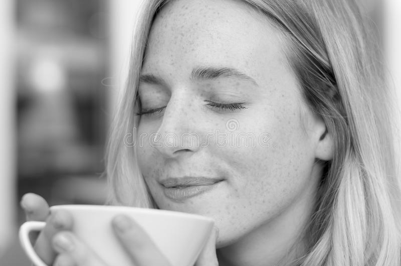 享用她的早晨咖啡的愉快的少妇 免版税库存图片
