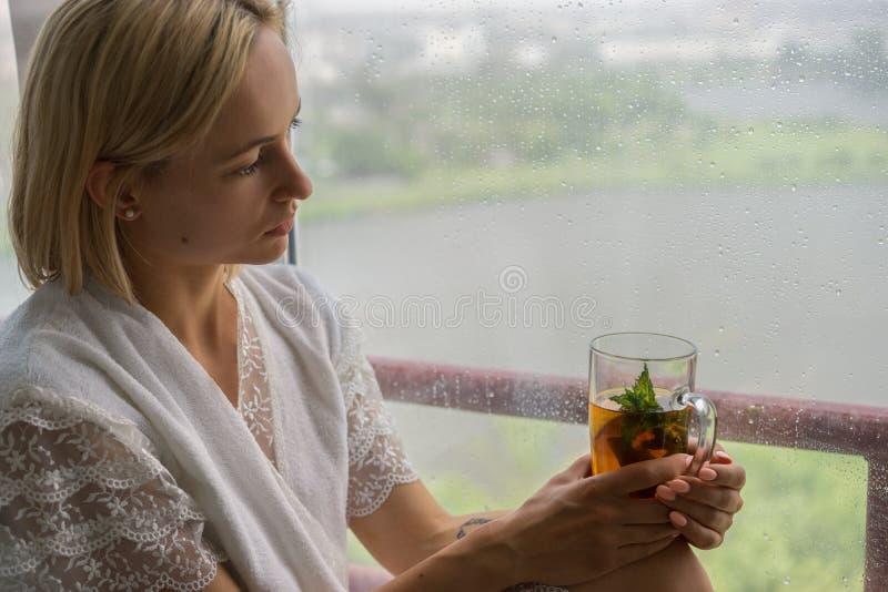享用她的早晨茶的少妇,看多雨窗口 美好浪漫无法认出女孩喝热 免版税库存照片