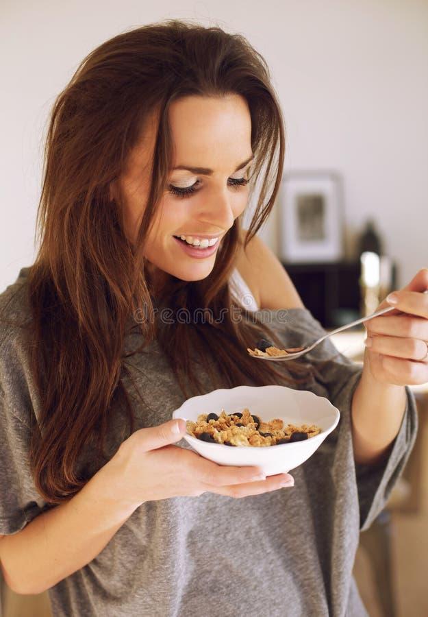享用她的早餐的微笑的妇女 库存图片