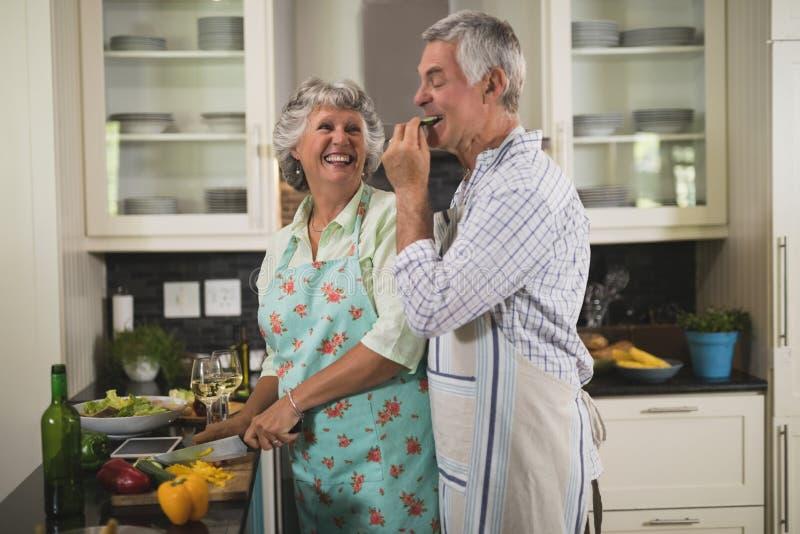 享用嬉戏的资深的夫妇,当烹调在厨房里时 免版税库存照片