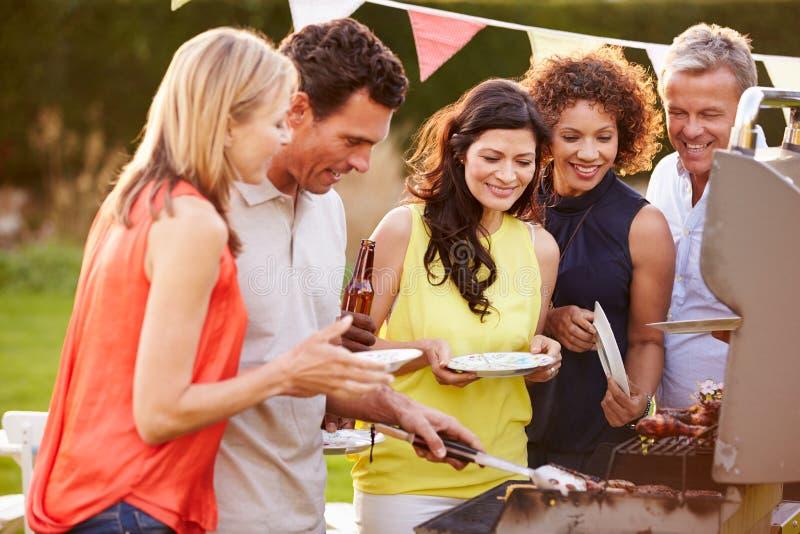 享用室外夏天烤肉的成熟朋友在庭院里 免版税库存图片
