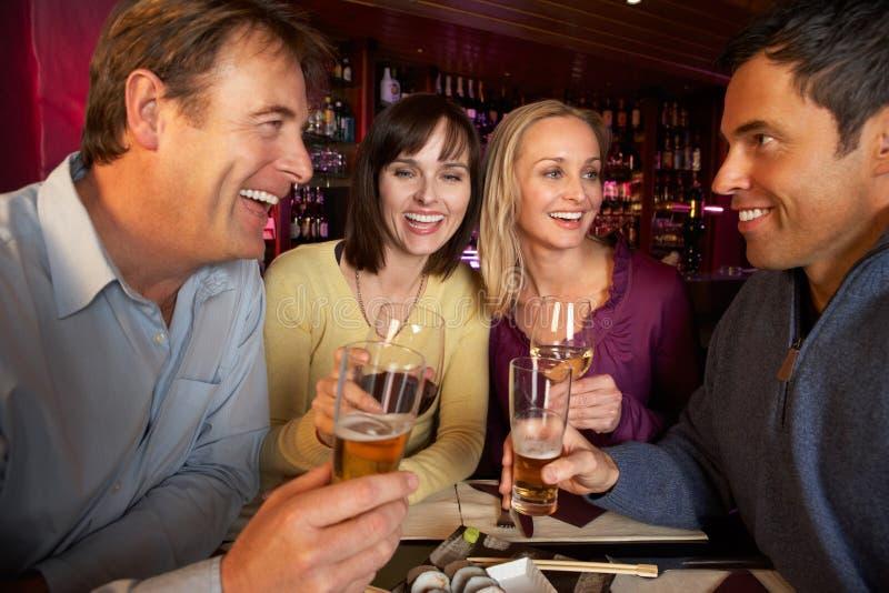 享用寿司的组朋友在餐馆 库存照片