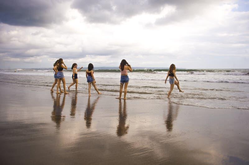 享用小组愉快和激动的少妇获得在美丽的日落海滩的乐趣在女朋友暑假一起绊倒 免版税图库摄影