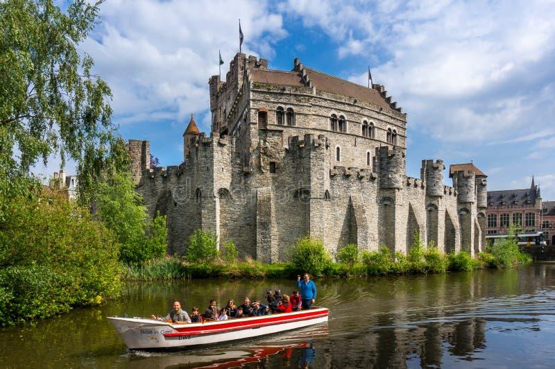 享用小船的游人在河乘坐在Gravensteen城堡附近 免版税库存图片