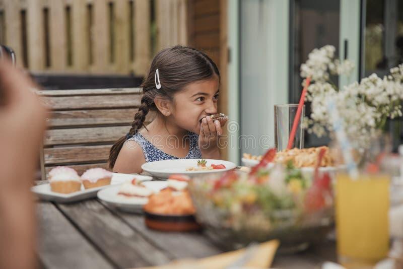 享用巧克力杯形蛋糕的小女孩 库存图片