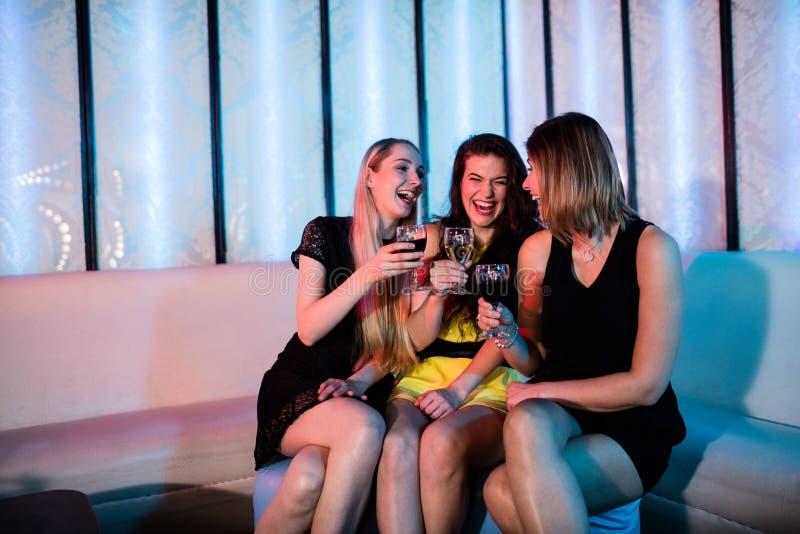 享用微笑的朋友,当饮用酒时 图库摄影