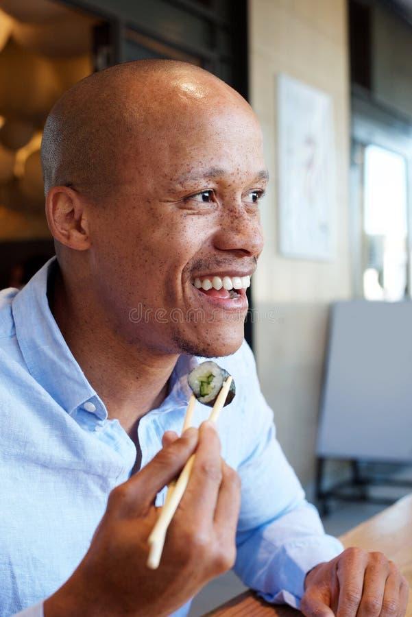享用微笑的非洲的人吃寿司 库存照片