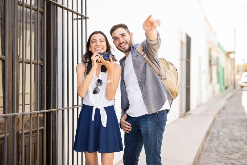 享用快乐的夫妇笑和点击照片 免版税图库摄影
