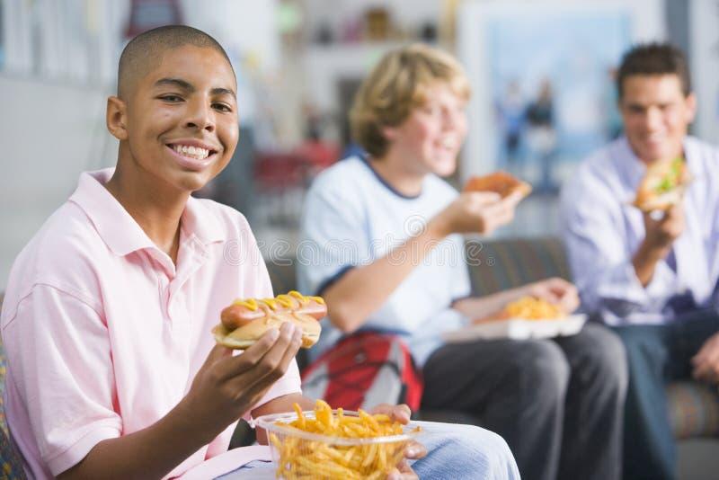 享用快餐的男孩一起吃午餐少年 免版税库存照片