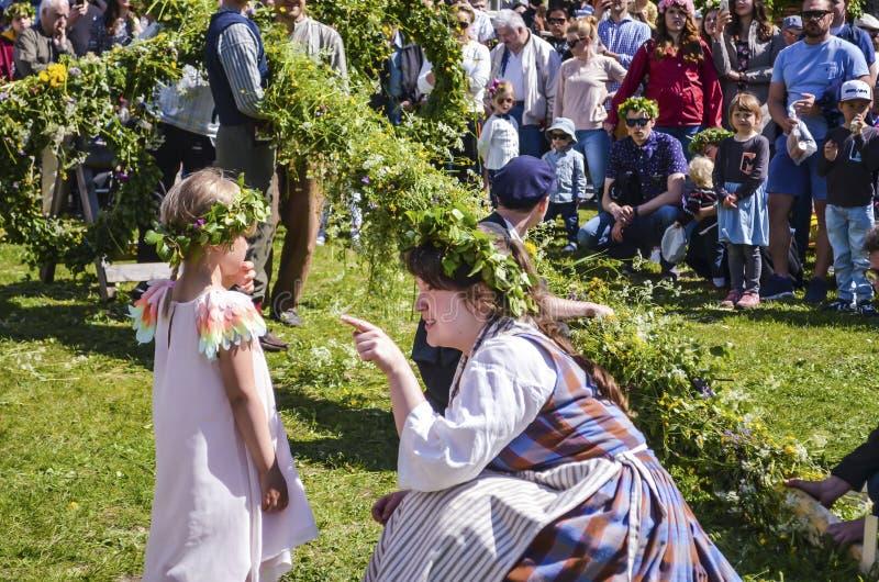享用愉快的人民观看杆身分片刻,当谈话与孩子和等待瑞典中间时的美女 免版税库存照片