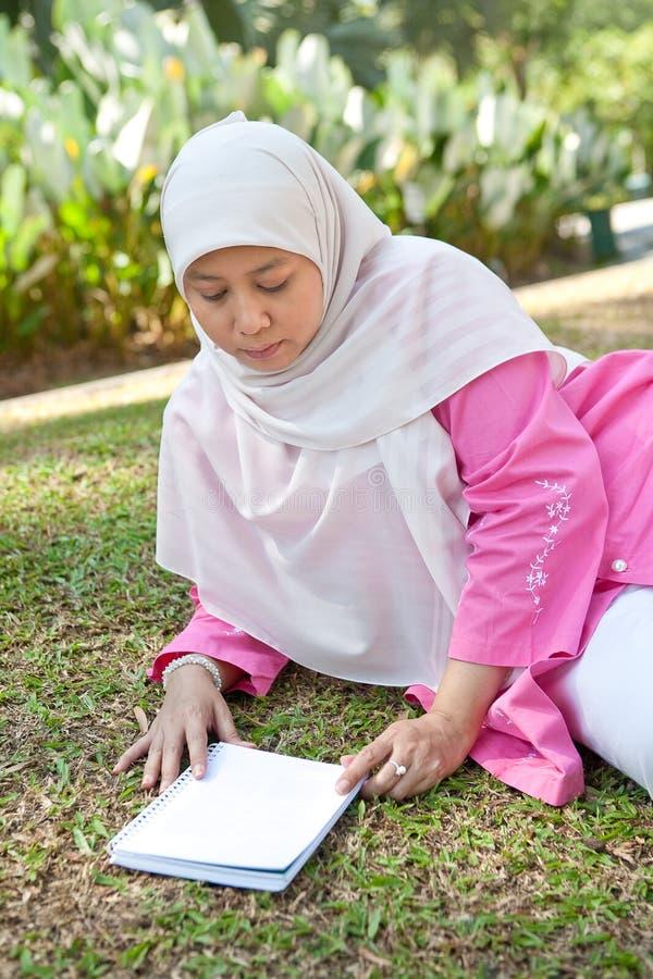 享用成熟回教公园妇女的书 免版税库存照片