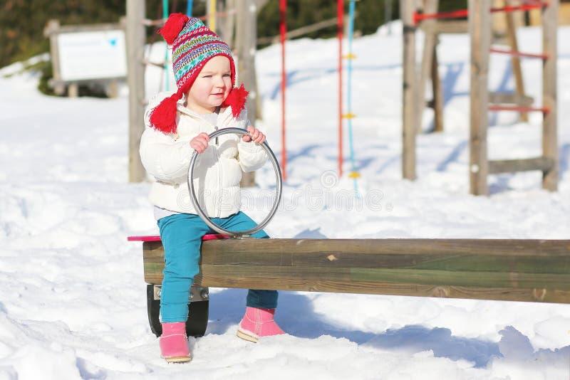 享用操场的逗人喜爱的女孩在冬天 库存图片