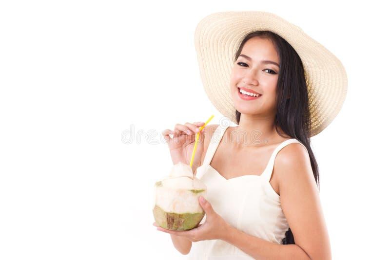 享用新鲜的椰子汁的愉快的夏天妇女 免版税库存图片