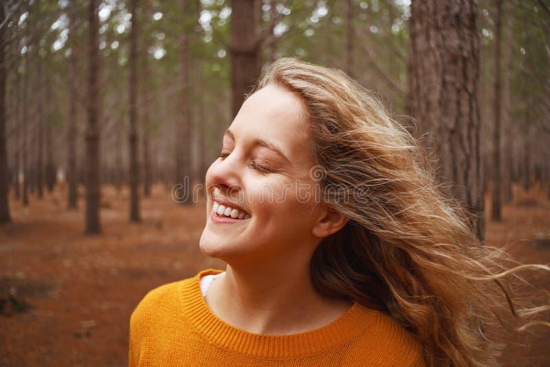 享用新鲜空气的微笑的年轻女人在森林里 免版税库存图片