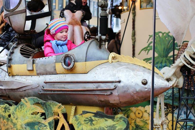 享用旋转木马的小女孩在游艺集市期间 免版税库存照片