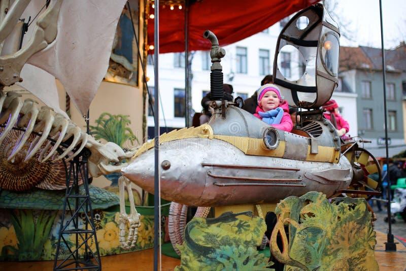 享用旋转木马的小女孩在游艺集市期间 图库摄影