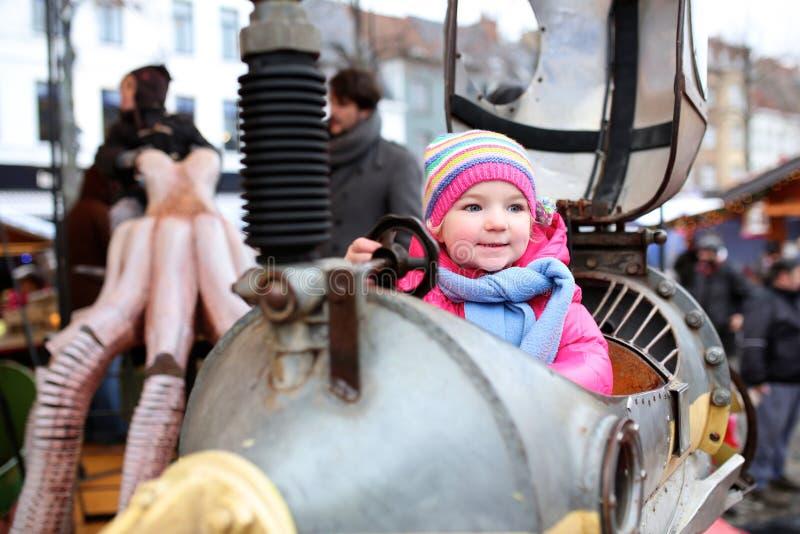 享用旋转木马的小女孩在游艺集市期间 免版税库存图片