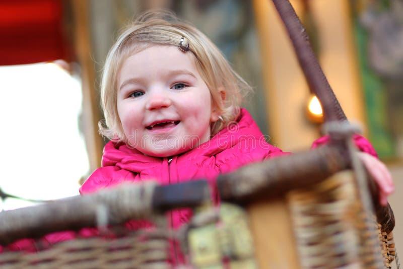 享用旋转木马的小女孩 免版税库存图片