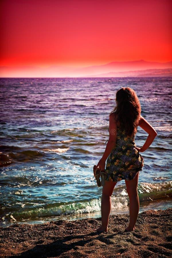 享用日落妇女的海滩 免版税库存照片