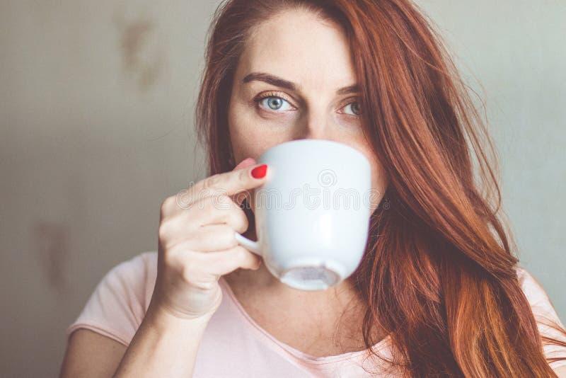 享用早晨咖啡的年轻女人 免版税库存图片