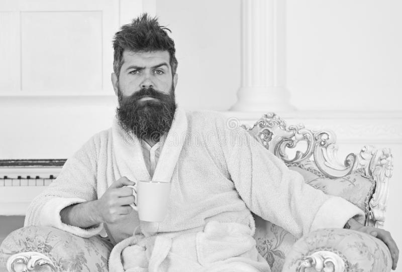 享用早晨咖啡的百万富翁 坐在白色背景的美丽的椅子的人 上升的人皱眉和他 免版税库存图片