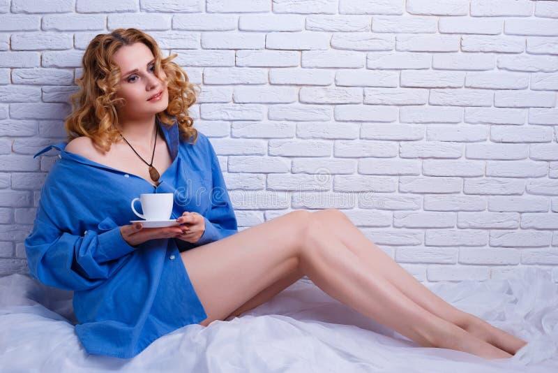 享用早晨咖啡的美丽的妇女坐在床上 Cozi 免版税图库摄影
