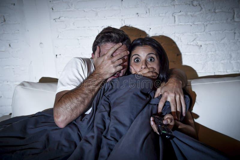 享用有吸引力的夫妇在家观看电视与毯子的恐怖片覆盖物 库存图片