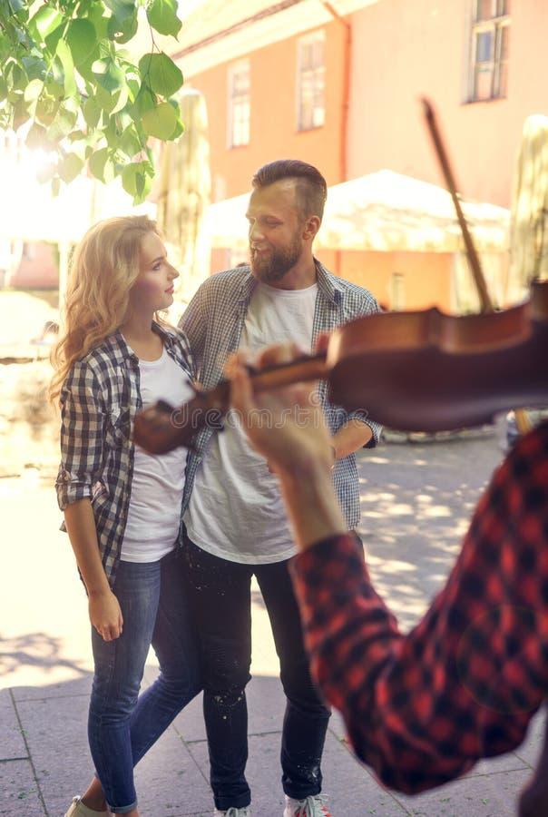 享用有小提琴的年轻爱恋的夫妇街道音乐家 图库摄影