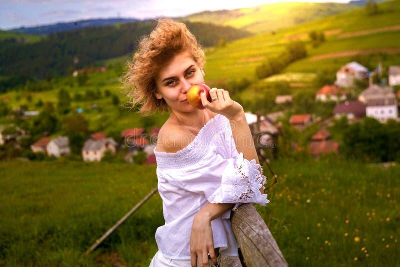 享用本质上,嗅到的花的年轻白肤金发的妇女 免版税图库摄影