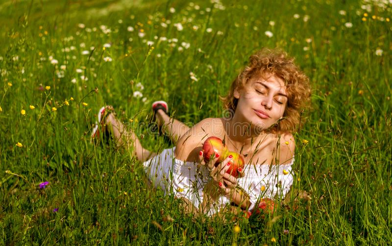 享用本质上,嗅到的花的年轻白肤金发的妇女 图库摄影