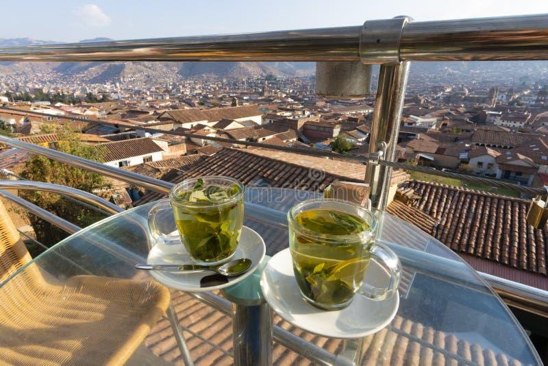 享用杯子古柯茶有库斯科市看法在秘鲁 免版税库存图片