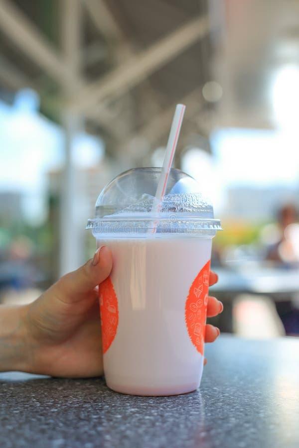 享用桃红色圆滑的人的妇女 拿着在一块玻璃的少女奶昔与在一个咖啡馆的秸杆外面在夏天 库存图片